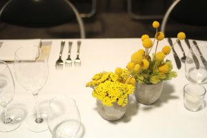 Yellow flowers on dinner table setting