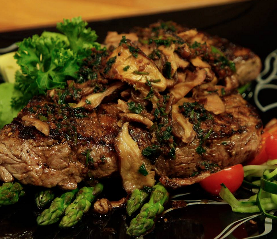 ta dish of seared steak on a bed of green vegetables